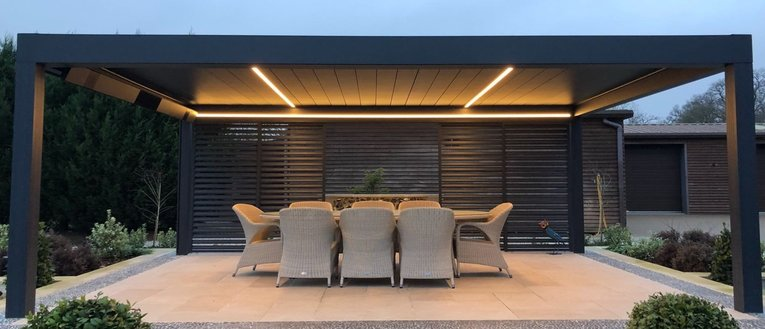 Link to page Renson Camargue Louvered Roof Canopy with Loggia sliding doors in a garden at nighttime