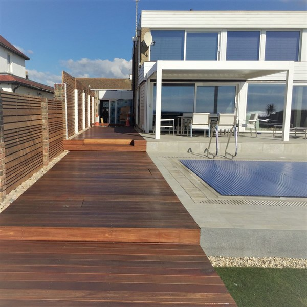 Large wooden decks frame a swimming pool