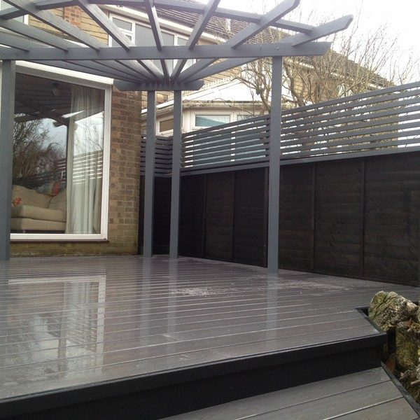 Raised deck with wooden pergola in a back garden