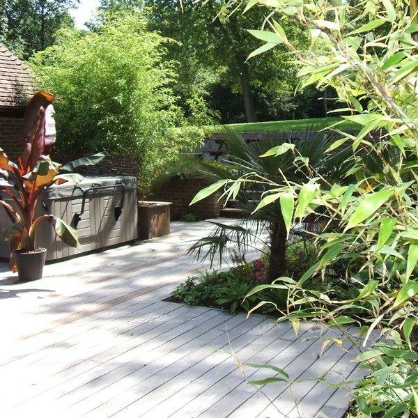 A decked walkway with a spa and numerous plants and planters