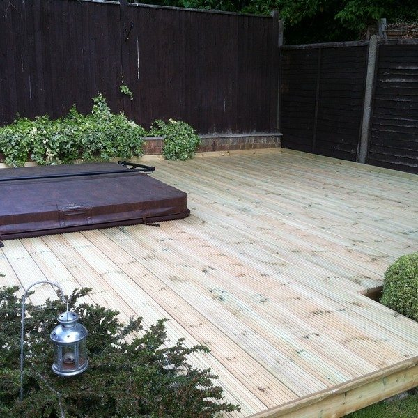 A sunken spa surrounded by wooden decking and numerous flower beds