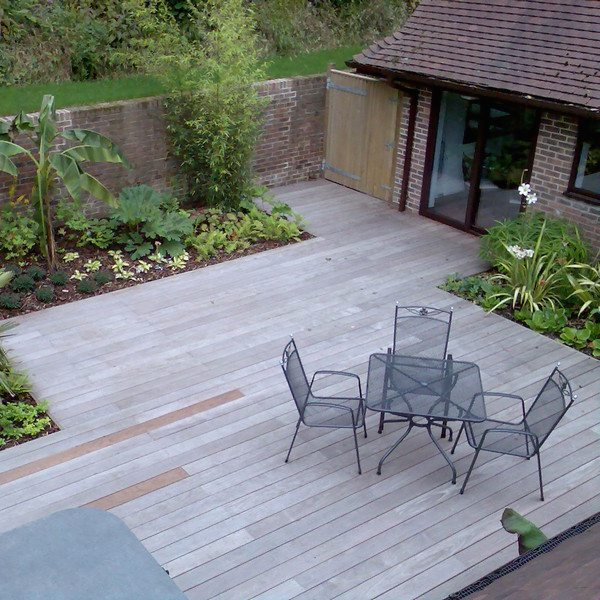 Wooden decking at the back of a house with some garden furniture and flower beds