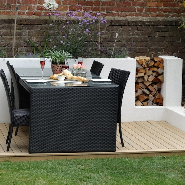 Decking used in an urban garden design with furniture and log storage