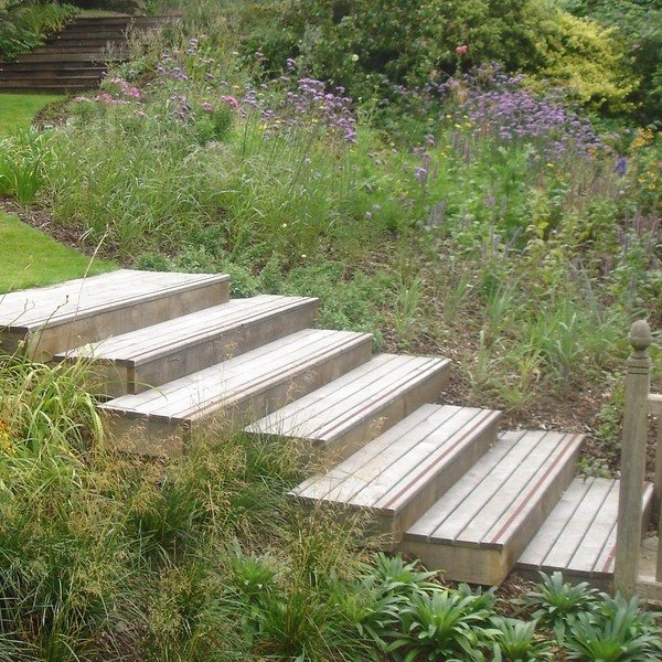 Wooden decking boards being used as steps in the garden path through the magnificent flower beds