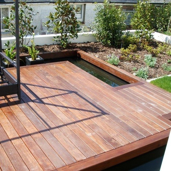 Wooden decking over a pond surrounded by flower beds