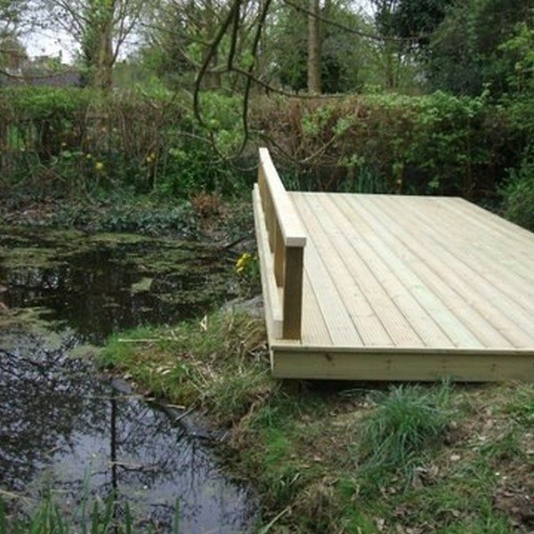 A wooden deck platform located next to a pond