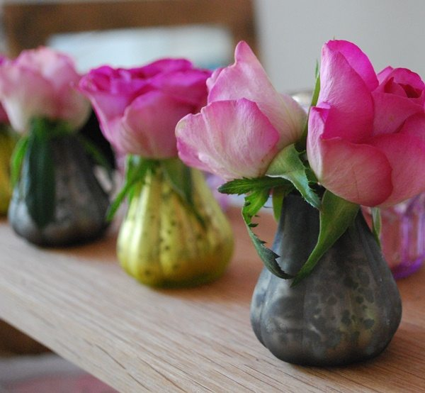 3 glass vases with single pink roses in