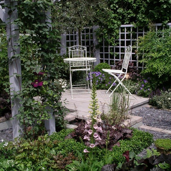 Bistro Dining Set In Decking Area Surrounded By A Plethora Of Plants