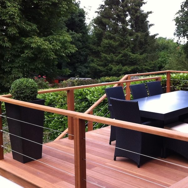 Raised decking with balustrades, garden furniture, and planters