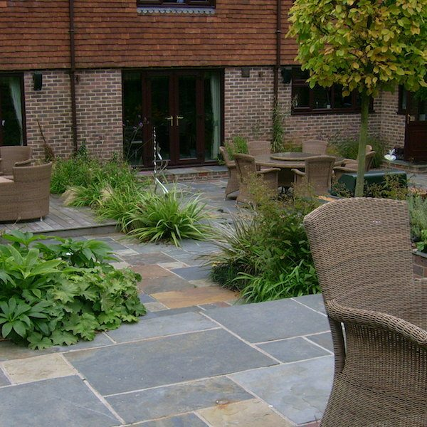 Back garden paved area with assorted planting beds and dining areas