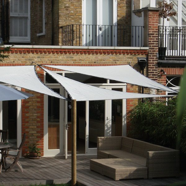 Sail shades and garden furniture on decking to create a tranquil outdoor living space