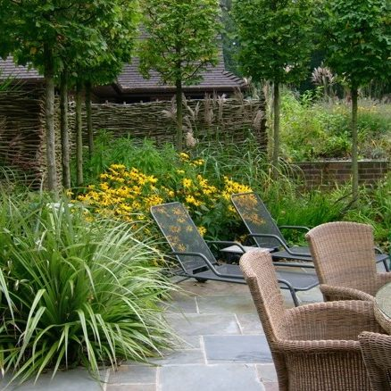 Unwind in a patio area with beautiful planting beds and garden furniture