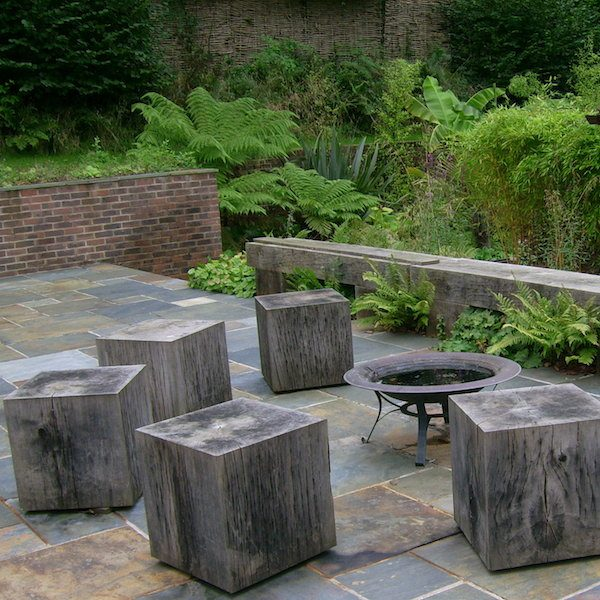 Wooden cube seats surrounding a fire pit on a paved patio