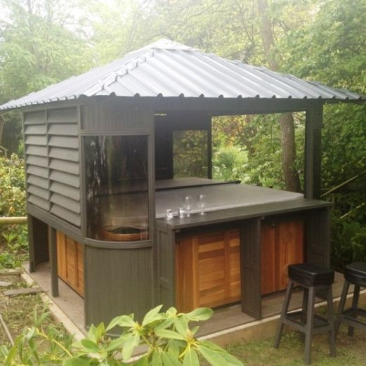 Hot Tub In Covered Outdoor Room With Seating Around The Edge