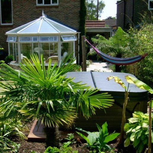 A hot tub surrounded by lush planting and a hammock