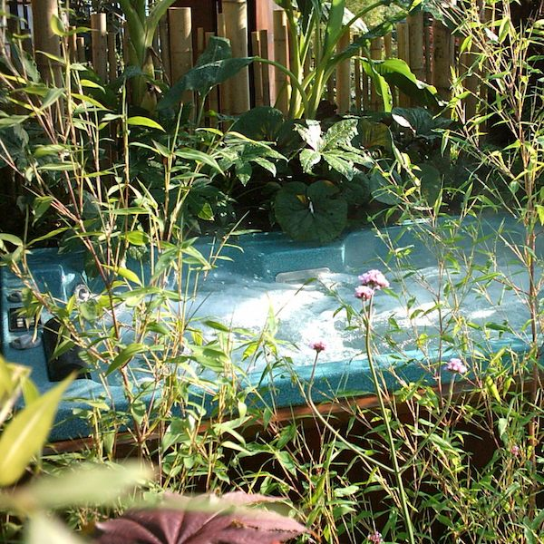 Hydropool hot tub surrounded by plants on display at a show garden
