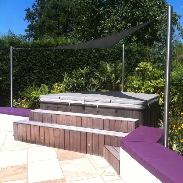 Hydropool hot tub covered by a right angle triangle Sail Shade on raised decking stairs