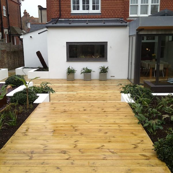 Raised decking with fibreglass Geo Cube planters and floral fancies along the walkway