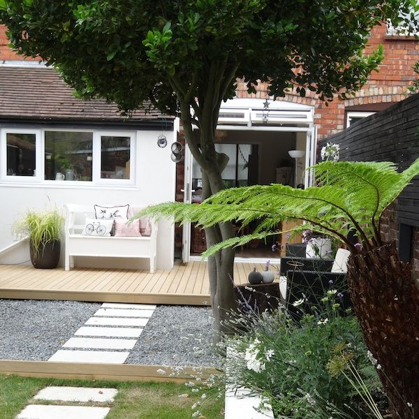 Outdoor decking area with pathway filled with pebbles leading to the rest of the garden