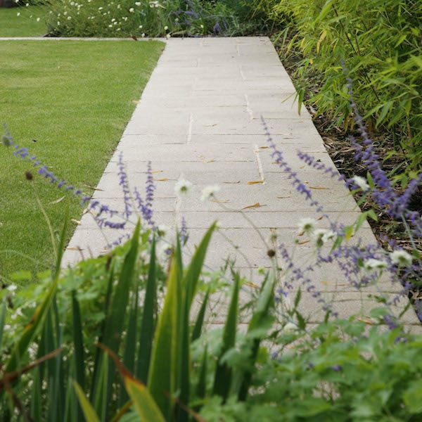 Paved pathway surrounded by grass and floral fancies