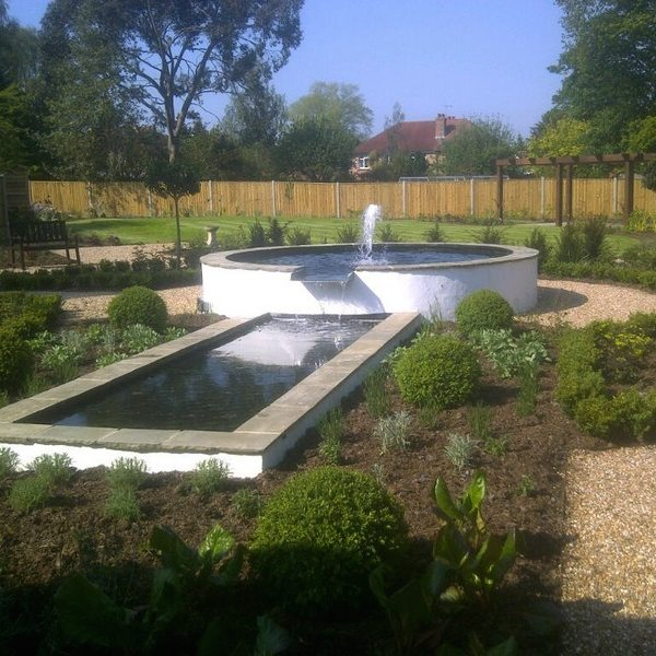 Fountain water feature with gravel path and planting surrounding