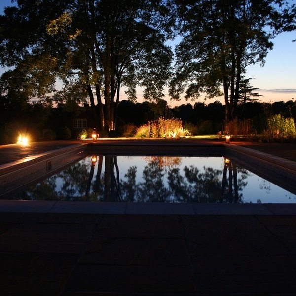 Gorgeous nighttime shot with lights and water feature installed by Garden House Design
