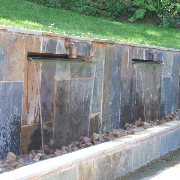 Water feature designed as a wall with two metal blades supplying the water to flow down